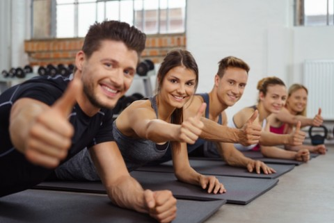 Group of men and women give the camera a thumbs up while on yoga mats in sports gym